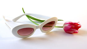 Sunglasses and tulip. A photo of white plastic sunglasses and red tulip Royalty Free Stock Photos