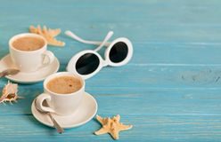 Sunglasses and two white cups of coffee on a wooden blue background. royalty free stock photos