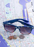 Sunglasses and U.S. coins on the map. Stock Photos