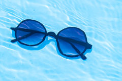 Sunglasses underwater in swimming pool Stock Photography