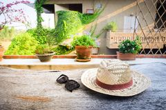 Sunglasses with vintage straw hat fasion on wooden table, Blur background for vintage resort hotel. Concept Summer royalty free stock photo