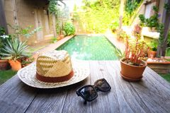 Sunglasses with vintage straw hat fasion on wooden table, Blur background for vintage resort hotel. Concept Summer stock images