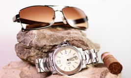 Sunglasses and watch on a stone Royalty Free Stock Photography