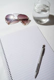 Sunglasses, water, pencil and notepad on a table from overhead Stock Image