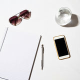 Sunglasses, water, phone and notepad on a table from overhead Stock Photo