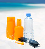 Sunglasses, water and sun protection cream. On beach background Stock Photography