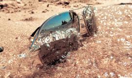 Sunglasses. Wave hits sunglasses on the beach Royalty Free Stock Images