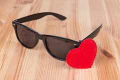 Sunglasses wayfarer with heart. Symbol over wooden background Stock Image