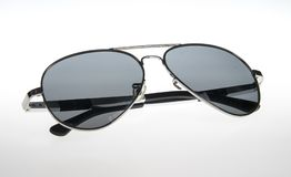 Sunglasses on a white background. Studio shot of sunglasses isolated on a white background. The glasses are tinted and reflective royalty free stock image