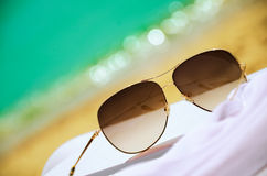 Sunglasses and white chiffon pareo on background of sea and sand Royalty Free Stock Images
