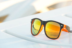 Sunglasses on a white plastic lounger Royalty Free Stock Photos