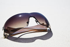 Sunglasses on white sand Stock Image