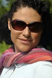 Sunglasses woman. This close up picture represents a woman wearing a sunglasses on a green back ground Royalty Free Stock Image