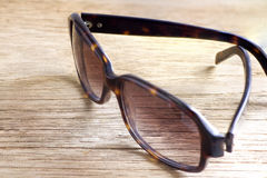 Sunglasses on a wooden table closeup Stock Images