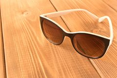 Sunglasses on wooden table. The concept of summer royalty free stock image