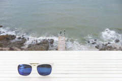 Sunglasses on wooden table with sea and beach Royalty Free Stock Photography