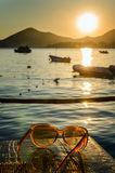 Sunglasses on wooden table at sunset Royalty Free Stock Photography