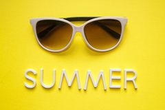 Sunglasses on yellow background and text summer. Top view. Holidays and vacation concept.  royalty free stock image