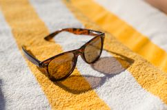 Sunglasses on yellow beach towel Stock Photos