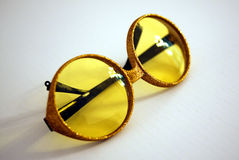 1960 sunglasses. Yellow 60's big round lenses sunglasses with glitter on it Royalty Free Stock Photo