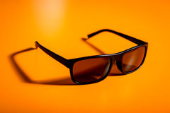 Sunglasses on the yellow table Royalty Free Stock Photos