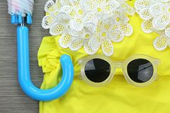 Sunglasses on yellow vintage bikini and umbrella, Beach items. Royalty Free Stock Images