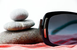 Sunglasses and zen stones on a beach towel Royalty Free Stock Images