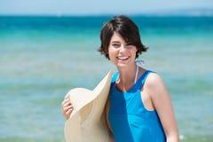 有她的sunhat的微笑的妇女在海边 免版税库存照片