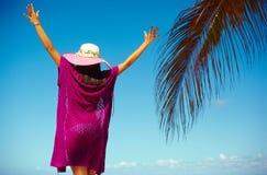 五颜六色的布料的性感的式样在蓝色海滩后的女孩和sunhat 免版税库存图片
