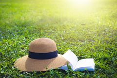 Sunhat and book lying on a lush green garden lawn under the hot rays of the sun royalty free stock image