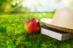 Sunhat, Buch und frischer Apfel Lizenzfreie Stockfotos