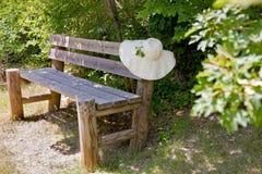 Sunhat en un banco de madera del jardín. foto de archivo