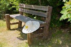 Sunhat en un banco de madera rústico. imagenes de archivo