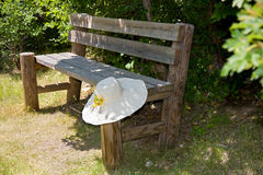 Sunhat on a rustic wooden bench. Stock Images
