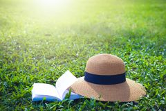 Sunhat y libro que mienten en un césped verde enorme del jardín bajo rayos calientes del sol fotos de archivo