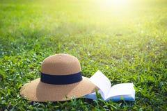 Sunhat y libro que mienten en un césped verde enorme del jardín bajo rayos calientes del sol imagen de archivo libre de regalías