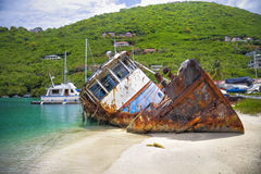 Sunk boat in the tropics. Sunk tug boat on the shoreline of a beautiful tropical island Royalty Free Stock Photography