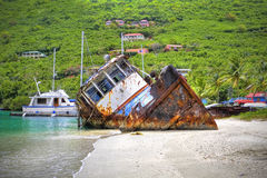 Sunk boat in the tropics. Old sunk tug boat on the shoreline of a beautiful tropical beach Royalty Free Stock Photos