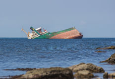 Sunk ship in blue water Royalty Free Stock Photography
