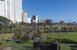 Sunked trädgårdar mot Beachfront stadshorisont för guld- mil arkivbild