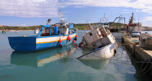 Sunken. Fishing boats at pier in the Maltese Port of Marsaxlokk. One of them are sunken near the pier Royalty Free Stock Image