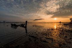 Sunken boat with distant jetty after sunrise Stock Images