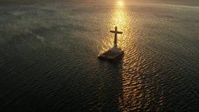 Sunken Cemetery cross in Camiguin island, Philippines. Catholic cross in sunken cemetery in the sea at sunset, aerial view. Sunset at Sunken Cemetery Camiguin stock footage