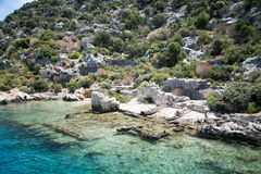Sunken city of Kekova in bay of Uchagiz view from sea. In Antalya province of Turkey with turqouise sea rocks and green bushes with remains of ancient city Royalty Free Stock Images