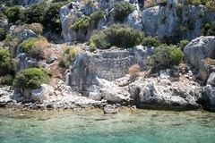 Sunken city of Kekova in bay of Uchagiz view from sea. In Antalya province of Turkey with turqouise sea rocks and green bushes with remains of ancient city Royalty Free Stock Photo