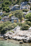 Sunken city of Kekova in bay of Uchagiz view from sea. In Antalya province of Turkey with turqouise sea rocks and green bushes with remains of ancient city Stock Photos
