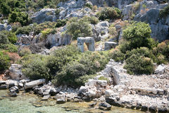 Sunken city of Kekova in bay of Uchagiz view from sea. In Antalya province of Turkey with turqouise sea rocks and green bushes with remains of ancient city Royalty Free Stock Photos