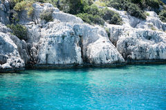 Sunken city of Kekova in bay of Uchagiz view from sea. In Antalya province of Turkey with turqouise sea rocks and green bushes Stock Photography