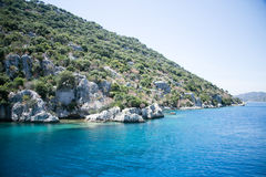 Sunken city of Kekova in bay of Uchagiz view from sea. In Antalya province of Turkey with turqouise sea rocks and greepn bushes Stock Photography