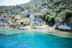 Sunken city of Kekova in bay of Uchagiz view from sea. In Antalya province of Turkey with turqouise sea rocks and greepn bushes with remains of ancient city Royalty Free Stock Photo